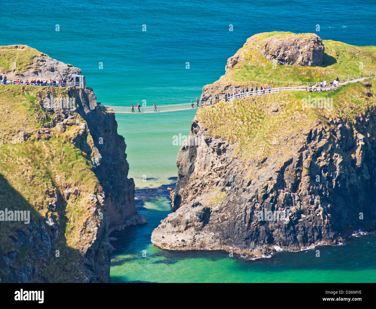 Tourists crossing the Carrick a rede rope bridge to Carrick island Ballycastle County Antrim Northern Ireland UK - Stock Image