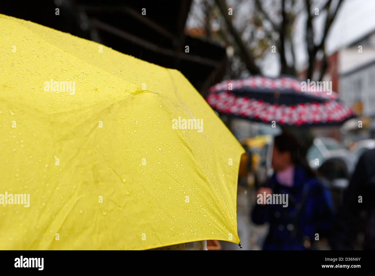 rain falling off a yellow umbrella on a wet rainy day in downtown Vancouver BC Canada - Stock Image