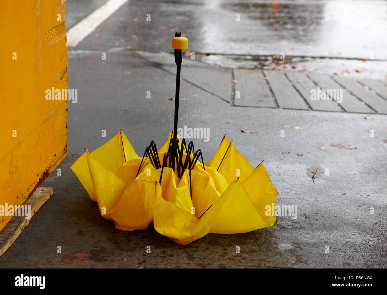 collapsed broken yellow umbrella on a wet rainy day in downtown Vancouver BC Canada - Stock Image