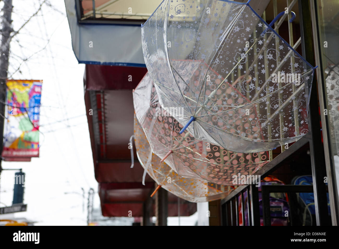 transparent umbrellas hanging outside on sale in a shop on a wet rainy day in downtown Vancouver BC Canada - Stock Image