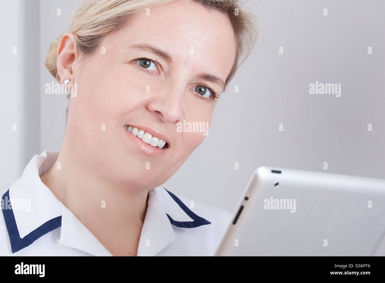 Female medical worker looking at camera holding a digital tablet. - Stock Image