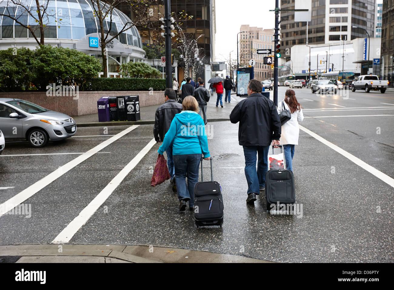 tourists walking across crosswalk on wet rainy day pulling wheeled luggage Vancouver BC Canada - Stock Image