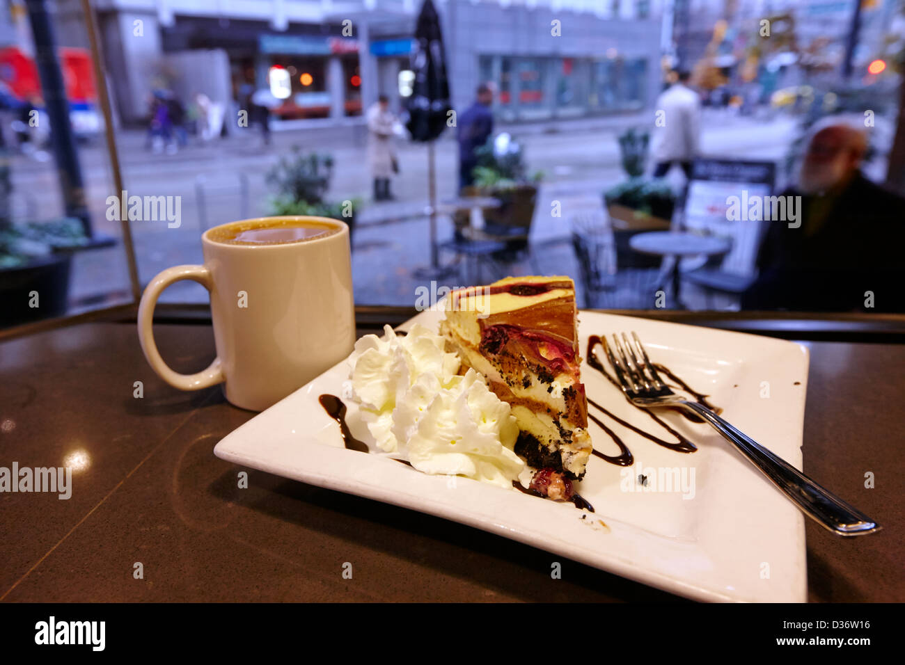 slice of luxury artisan sin cheesecake with cup of coffee in a trees organic coffee house Vancouver BC Canada - Stock Image