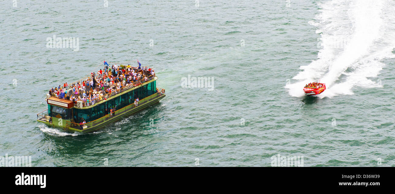 Passengers enjoying Australia Day in Sydney harbour watching a passing Jet boat - Stock Image