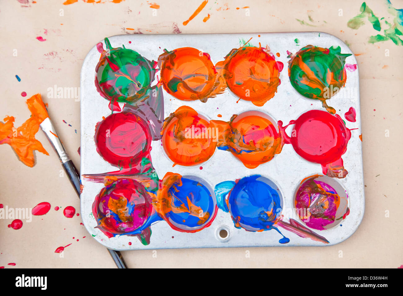 Messy array of colors of children's paint in a tray with a paint brush. - Stock Image