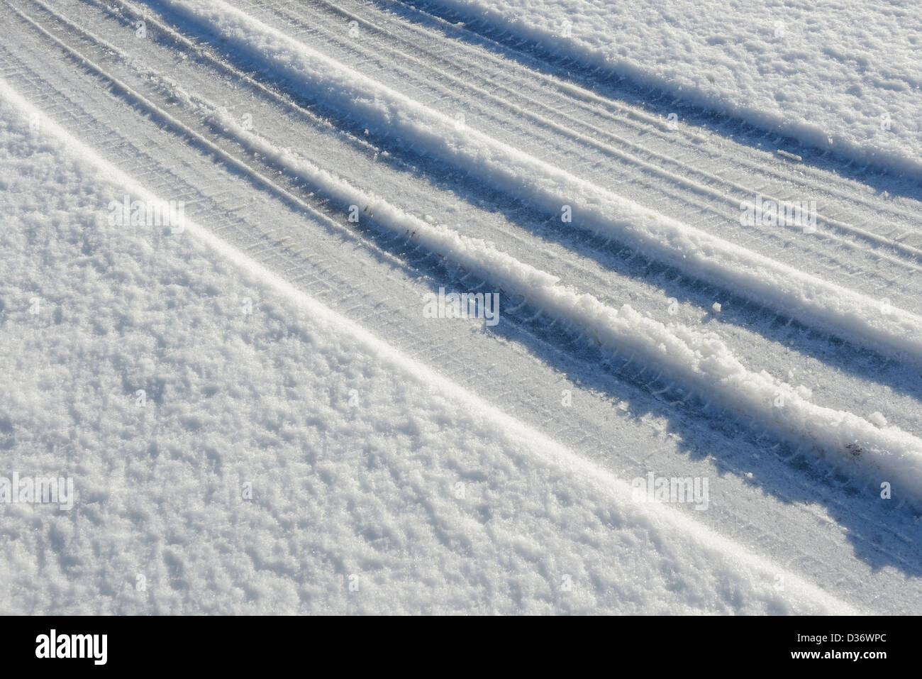 Car tyre tracks in fresh snow - Stock Image