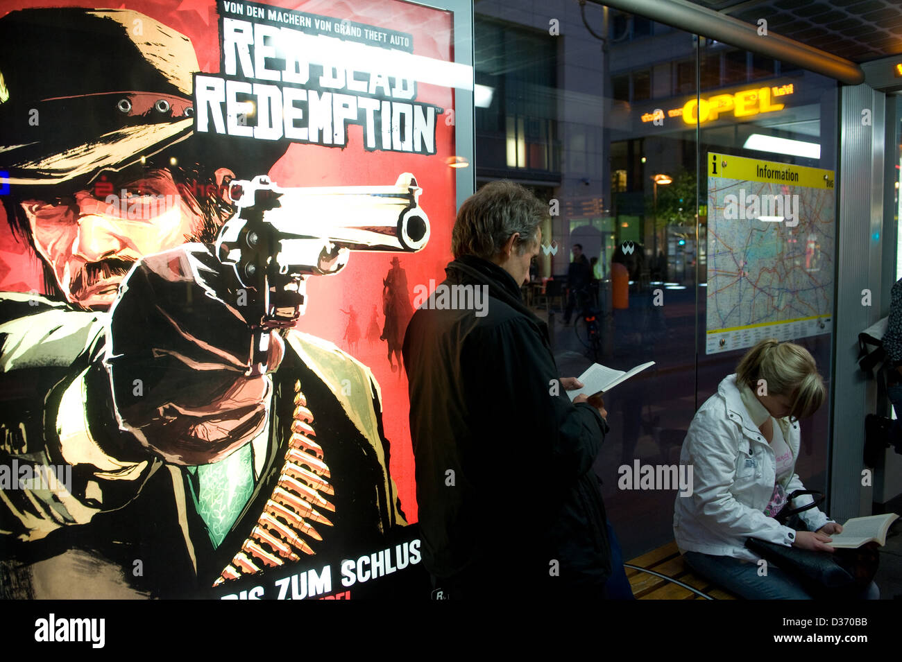 Berlin, Germany, a reading man before advertising for the western shooter Red Dead Redemption - Stock Image