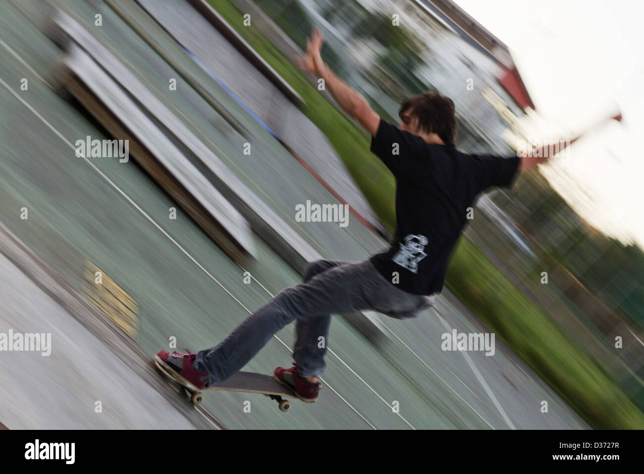 skateboarder with red shoes dose trick with blurred background and diagonal composition East London South Africa - Stock Image