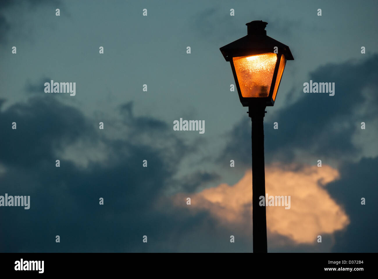 The warm glow from a lamp post appears to illuminate a cloud in the last light of dusk. - Stock Image
