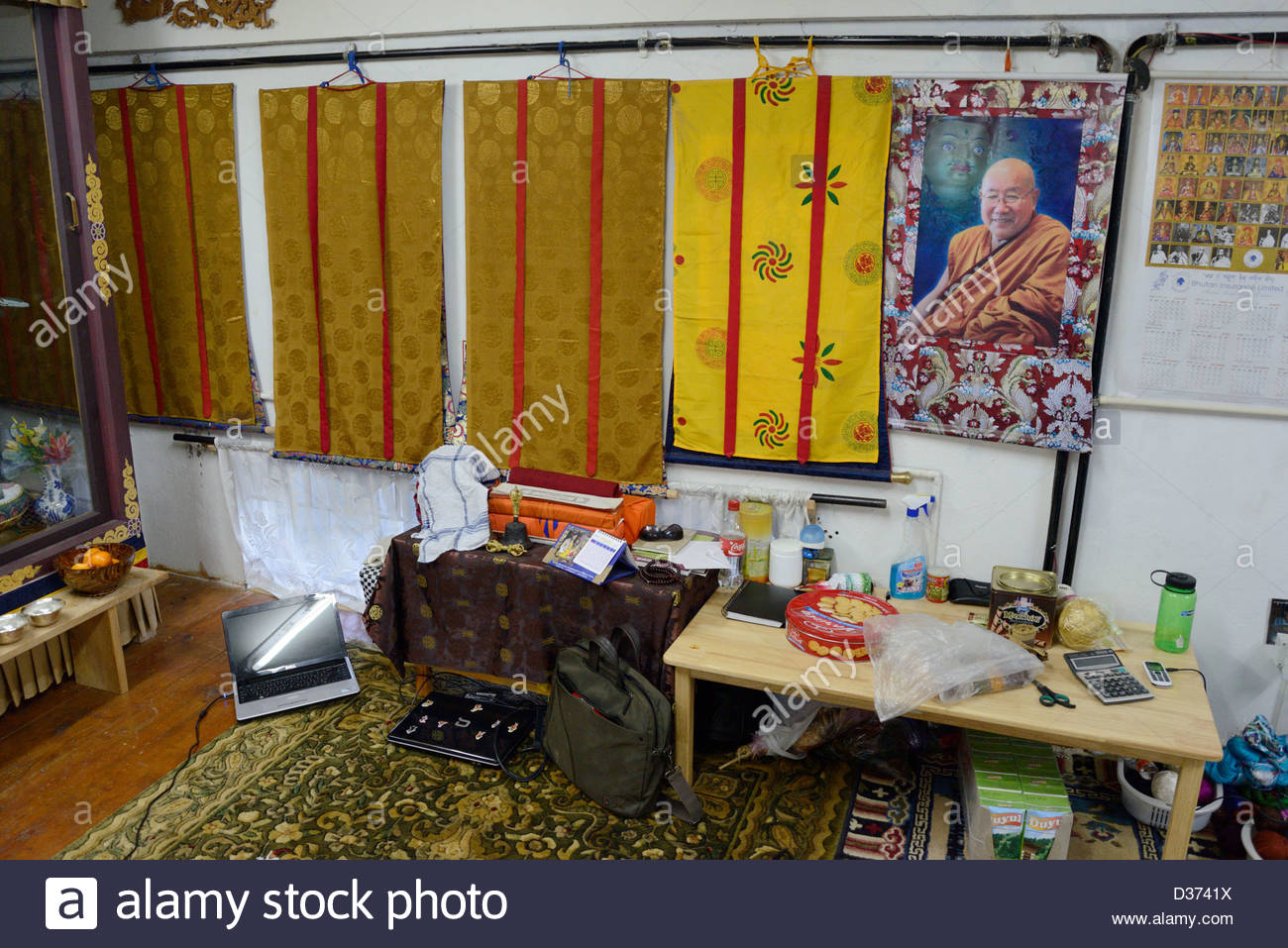Office living area of Bhutanese weaving shop,Dell laptop,biscuits,cartons of juices,Buddhist calendar,shrine to - Stock Image
