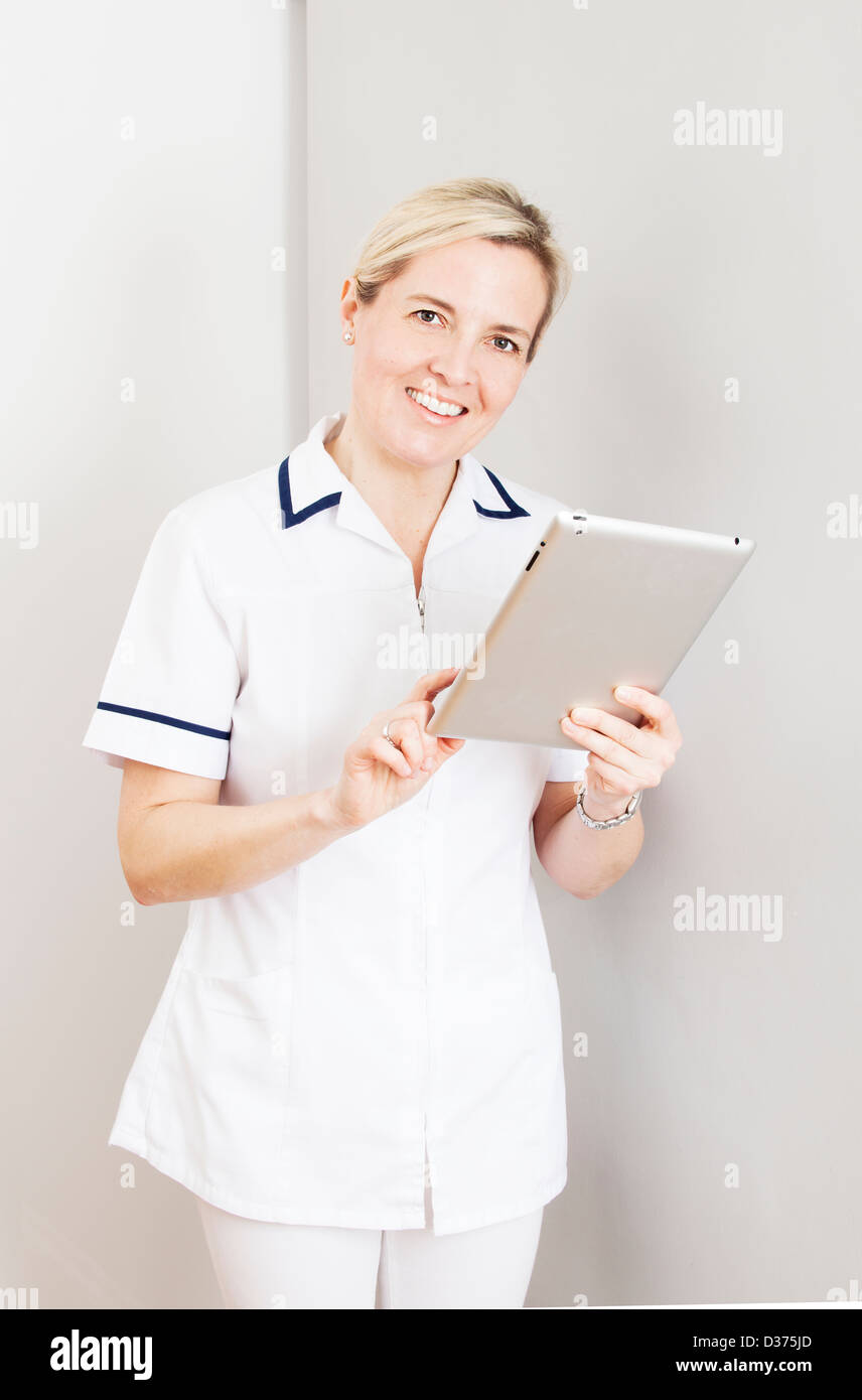 Smiling female wearing a white medical uniform holding a digital tablet. - Stock Image