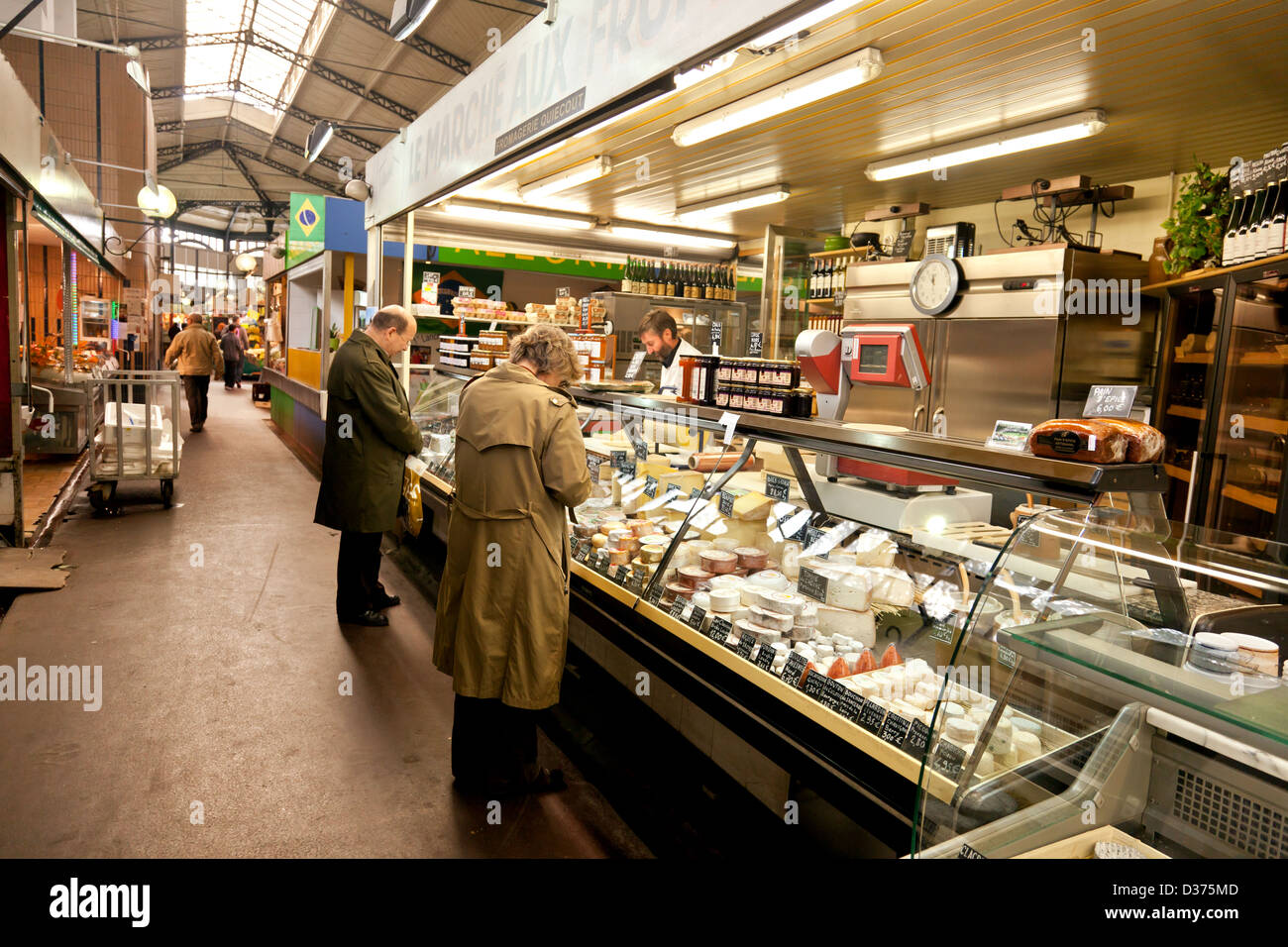 Customers and a stallholder at Le Marché aux Fromages, a cheese stall in the Marché Saint Quentin in central - Stock Image