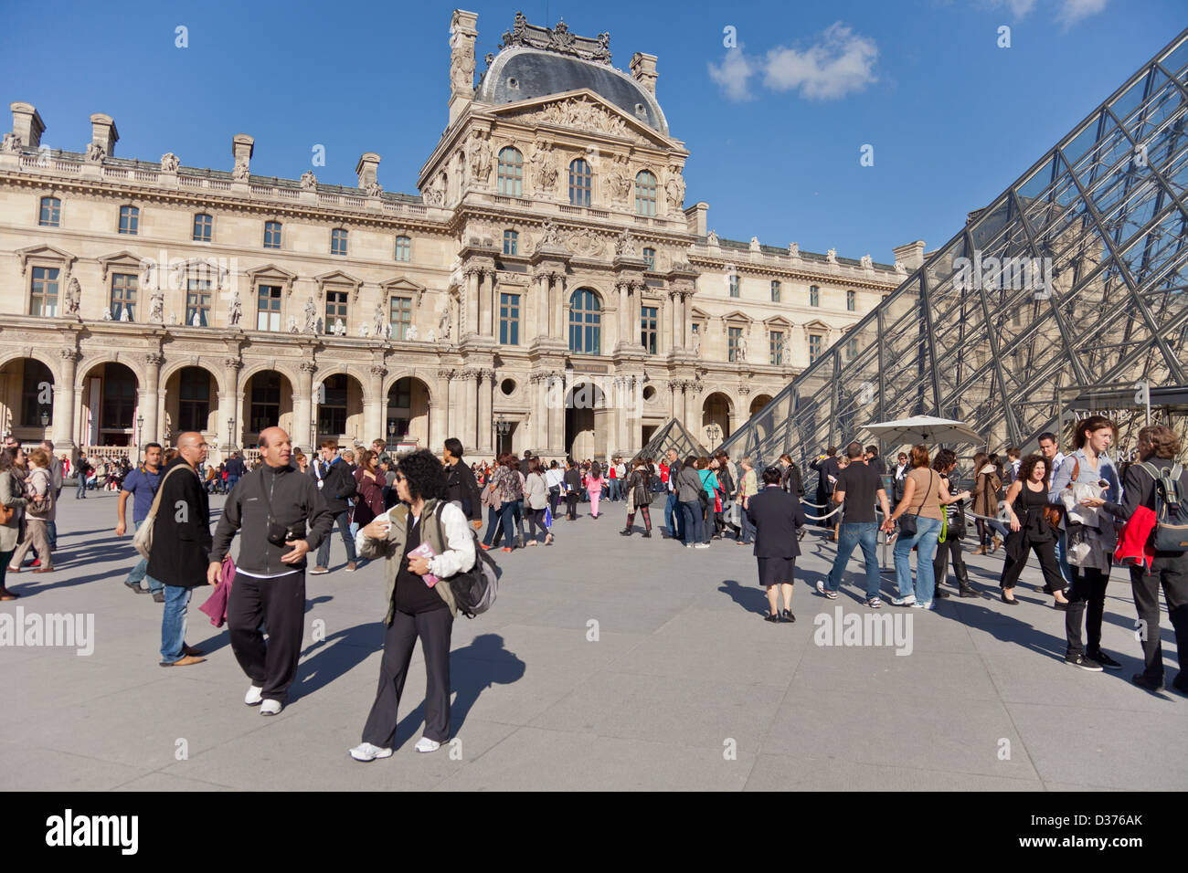 People in courtyard of the Louvre in Paris, France: the world's most visited museum. Pei's glass pyramid - Stock Image