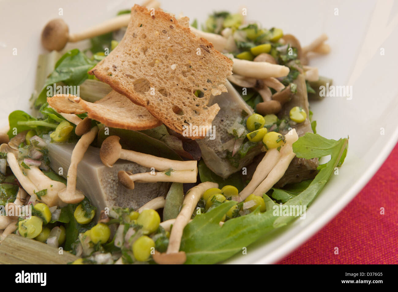 Artichoke salad with pickled shimeji mushrooms and peas served on a ...