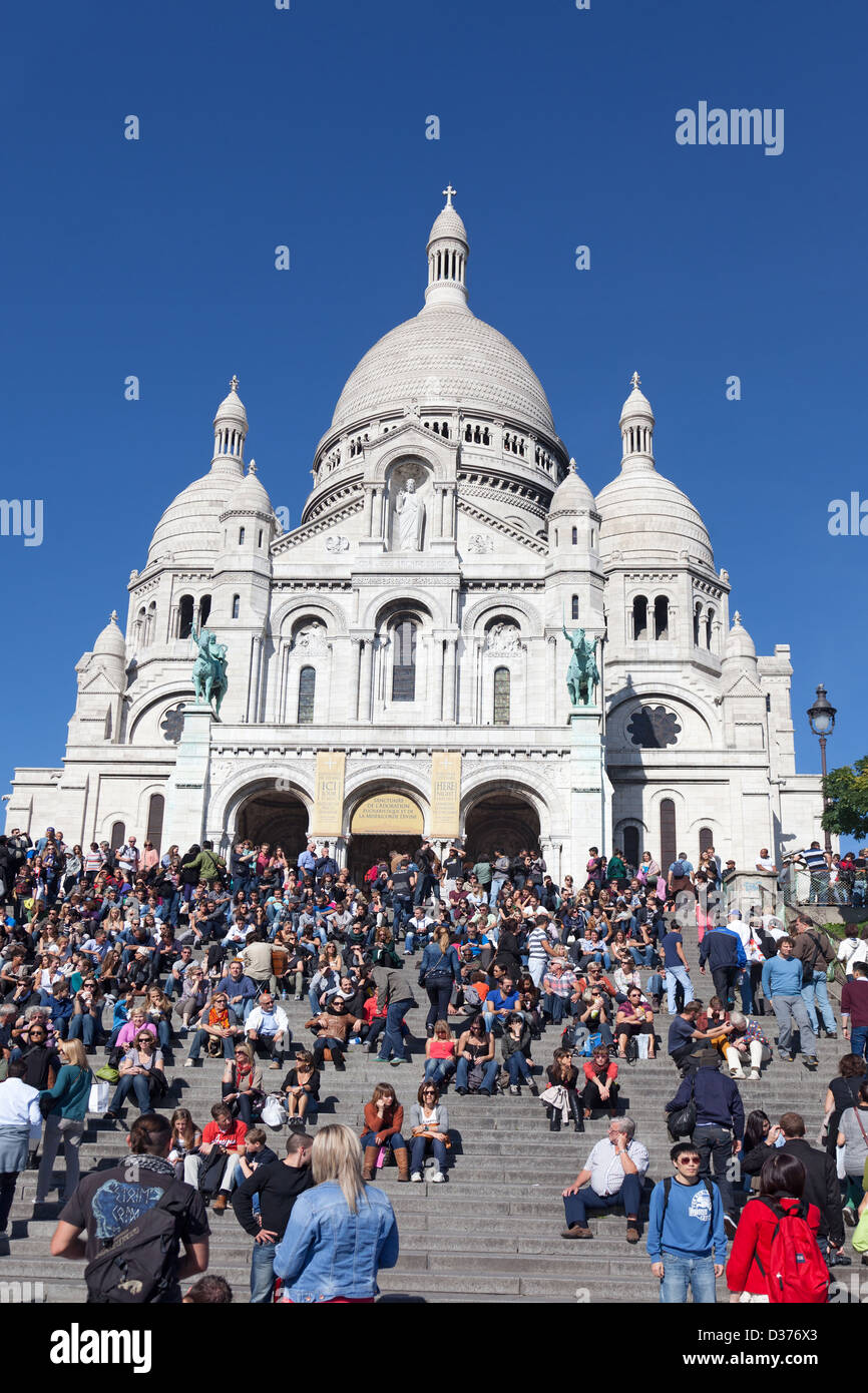 A large crowd of people standing, walking or sitting on the steps leading up to Sacre Coeur basilica in Montmartre, - Stock Image