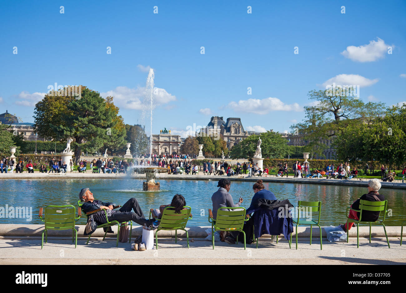 People enjoying some autumn sunshine around the edge of a pond: Jardin des Tuileries, Paris. Louvre museum in background. - Stock Image