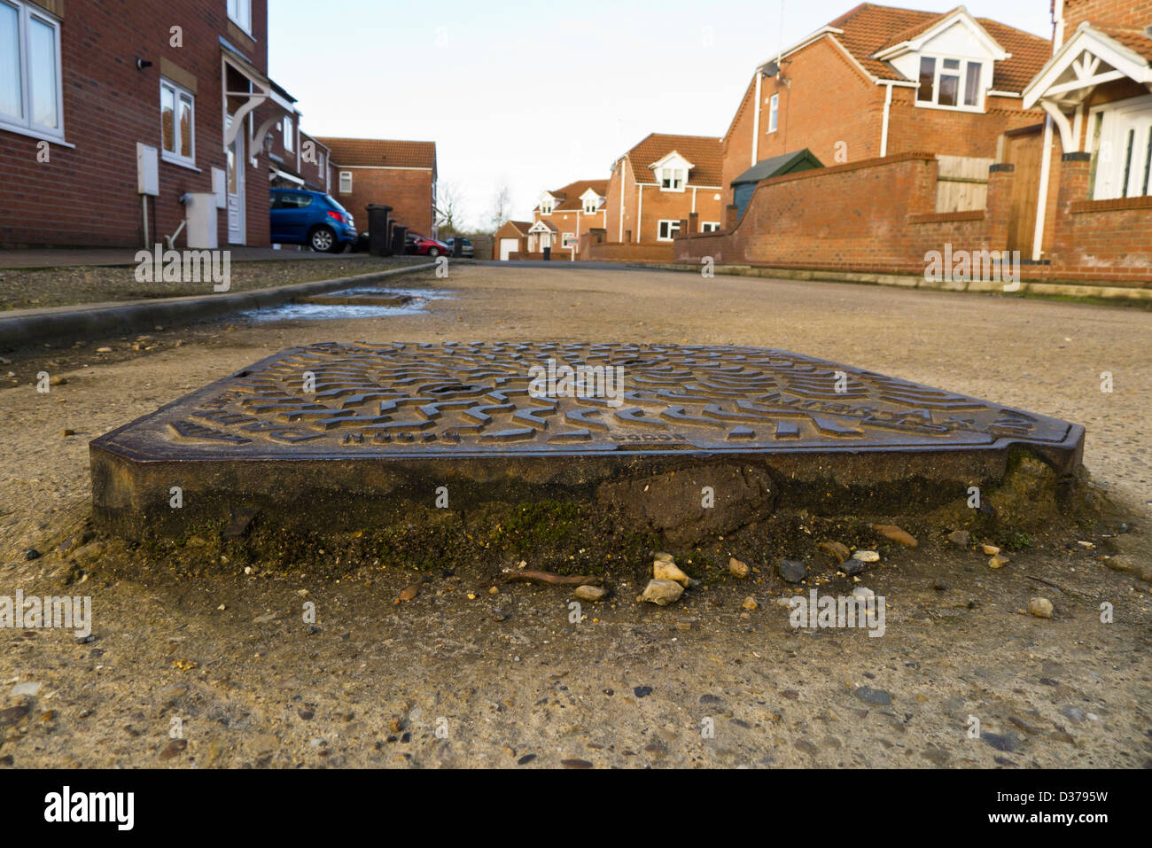 A raised manhole cover on a poorly surfaced road in King's Lynn, Norfolk. - Stock Image
