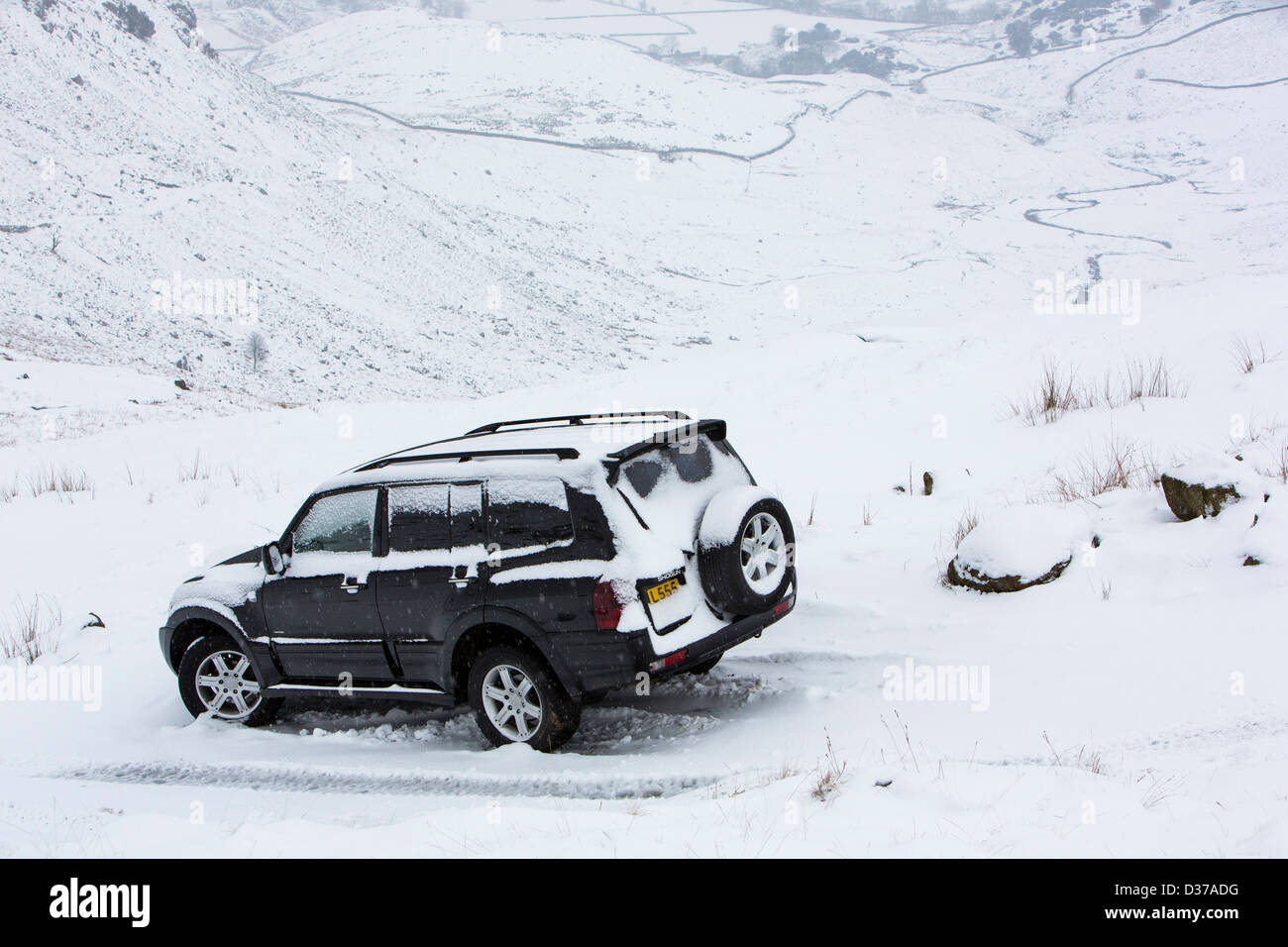 A chelsea tractor abandoned on Wrynose Pass after the fool driver attempted to drive over in Winter conditions - Stock Image