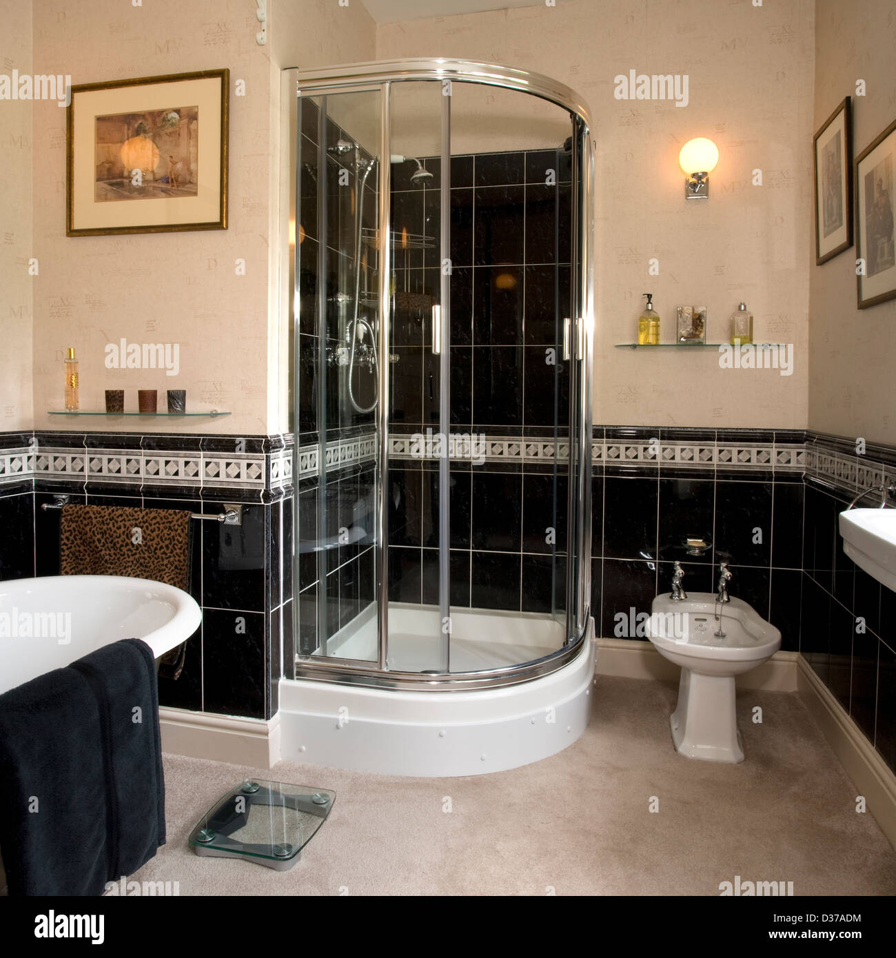 A shiny chrome and black tiled bathroom with shower Stock Photo ...