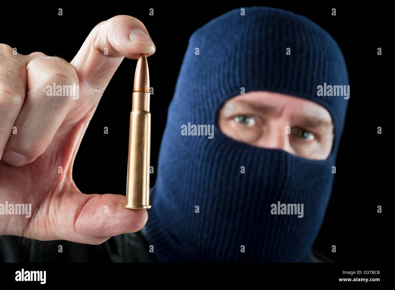 A terrorist wearing a ski mask as a disguise holds out a large automatic rifle bullet. - Stock Image
