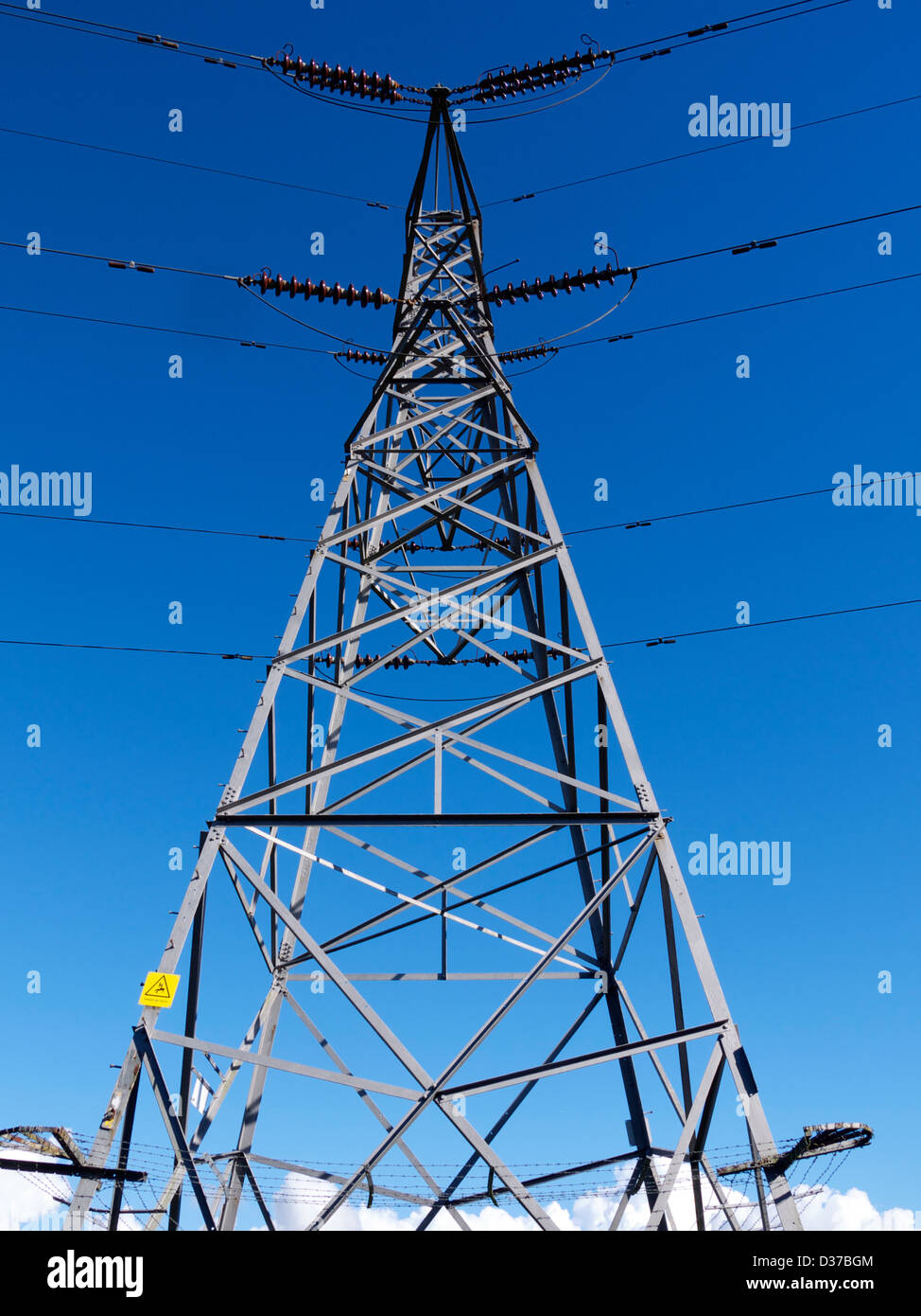 A electricity pylon against a blue sky - Stock Image