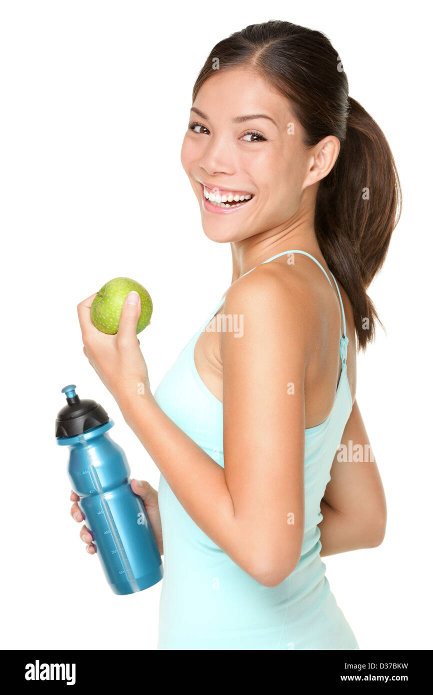 Portrait of smiling Asian Caucasian woman holding apple and water bottle isolated on white background - Stock Image