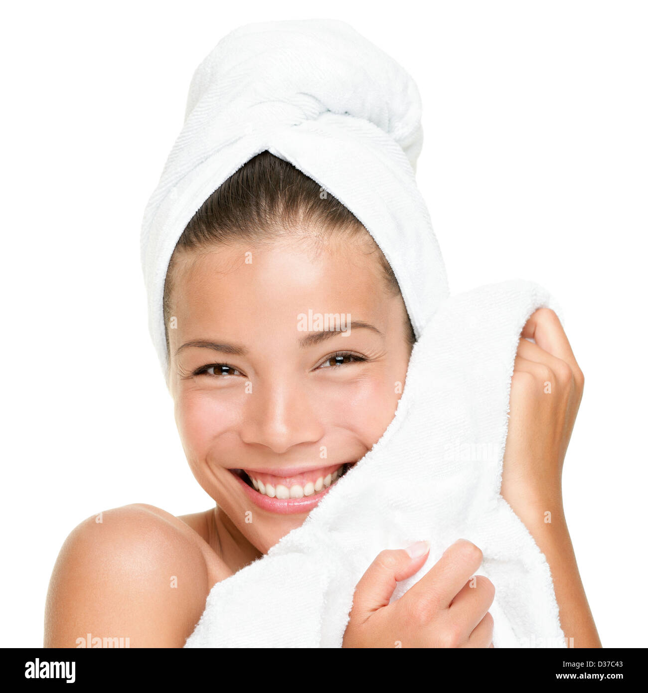 Closeup portrait of beautiful smiling Chinese Asian / Caucasian woman feeling soft towel on face isolated on white - Stock Image