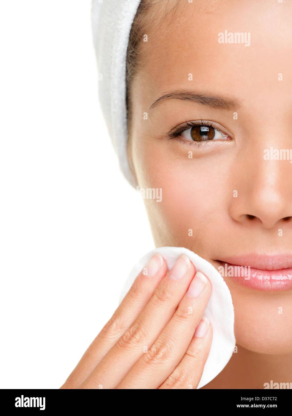 Closeup portrait of pretty beautiful mixed race woman removing face makeup with cotton swab pad isolated on white - Stock Image