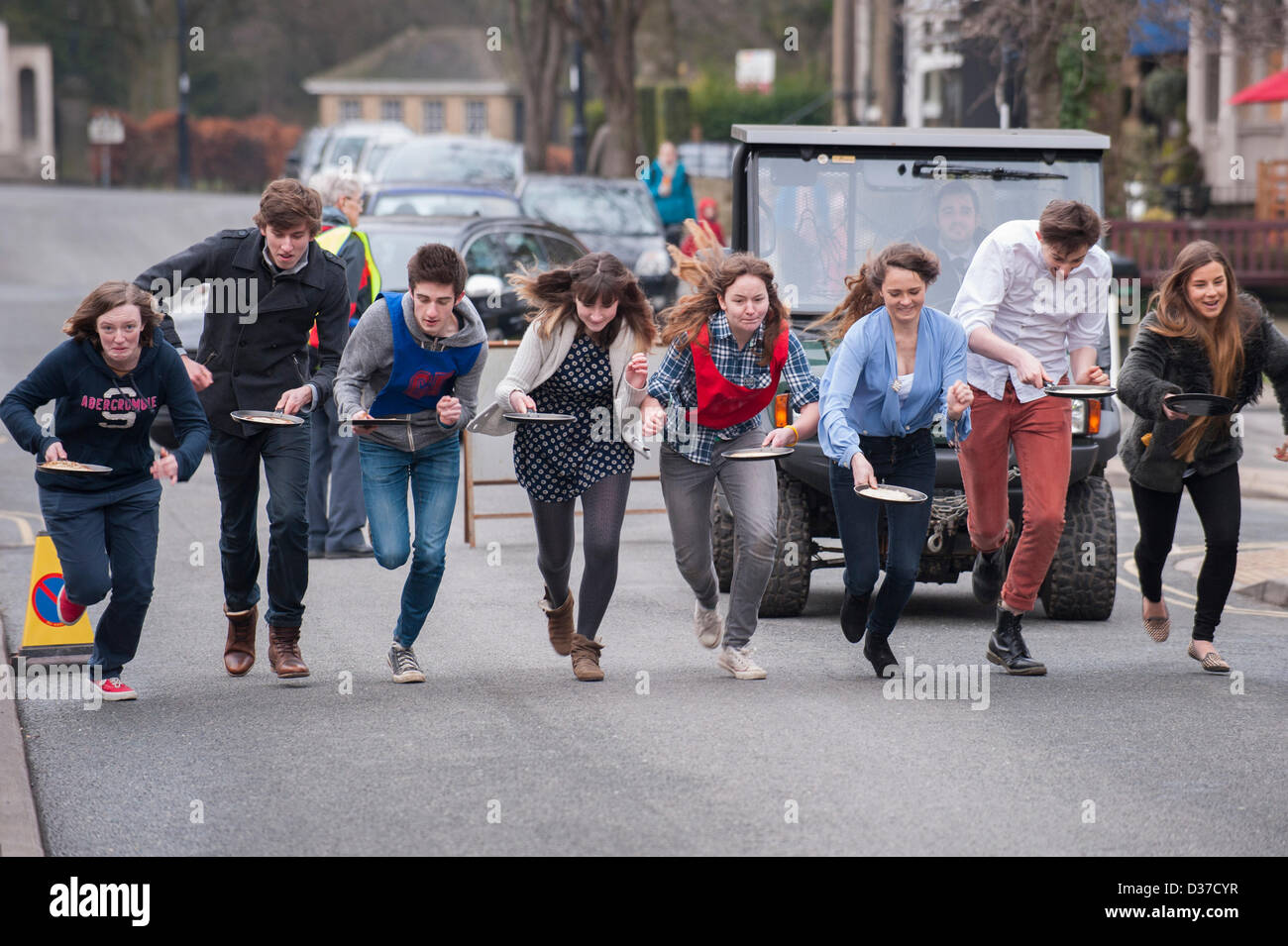 Competitors (male & female teenagers) with frying pans, taking part, running & racing in traditional Pancake Race Stock Photo