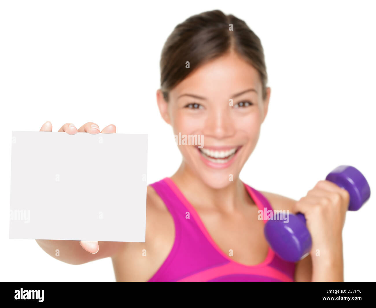 Portrait of smiling woman with dumbbells showing empty blank paper sign isolated on white background - Stock Image