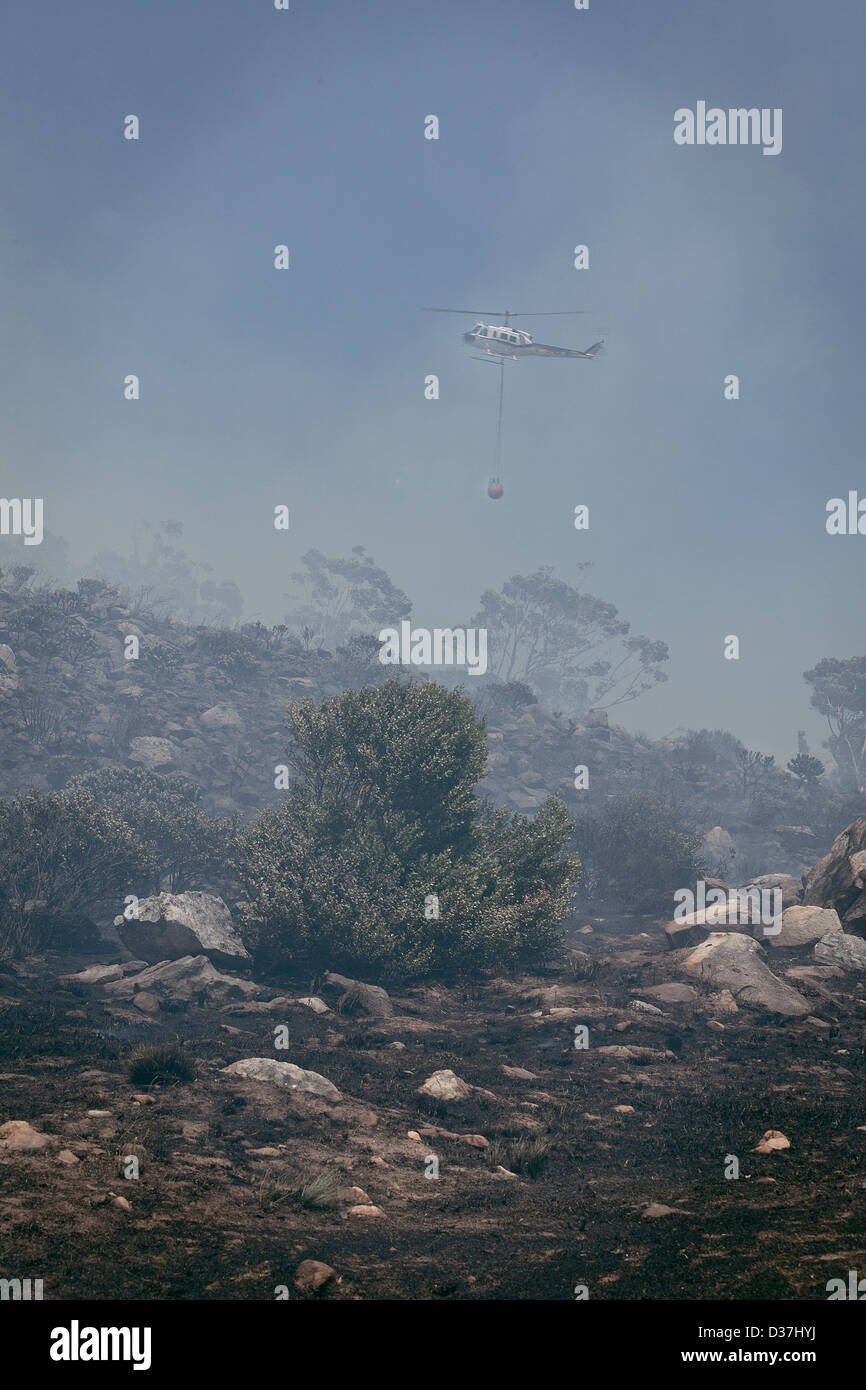 A yellow Helicopter is used to bring raging fires in Hout Bay under control. Stock Photo