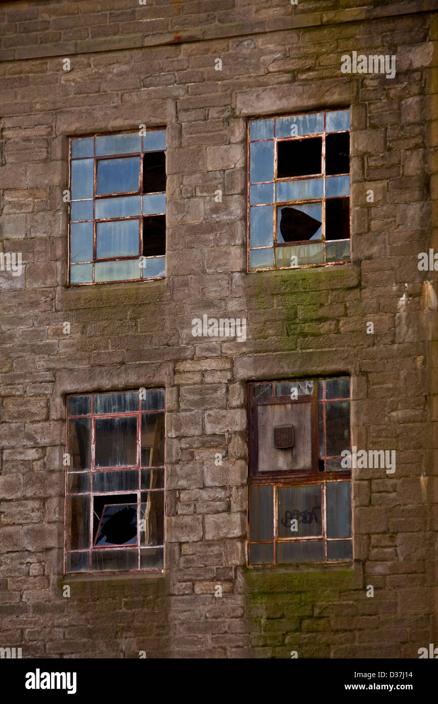 Four broken windows on the side wall of the famous 1800`s 'Baxter Brothers' Jute Mill in Dundee,UK - Stock Image