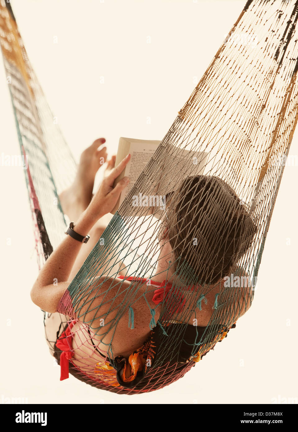 Woman reading book in hammock - Stock Image
