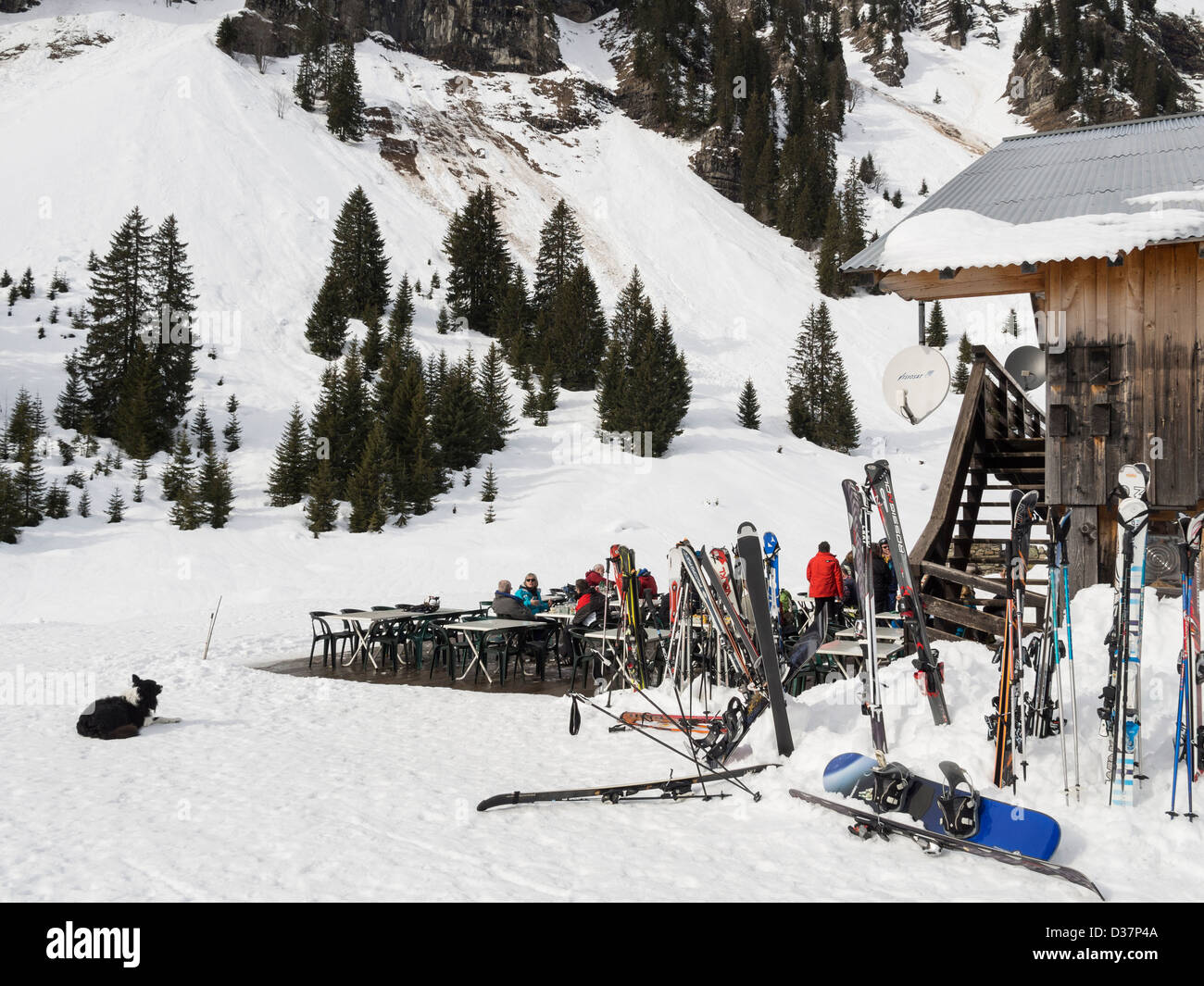 Skis and people outside Gite du Lac de Gers lakeside ski restaurant in Le Grand Massif in French Alps near Sixt - Stock Image