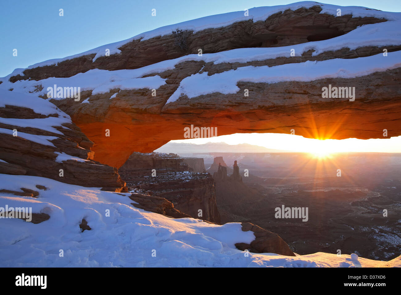 Mesa Arch covered in snow and sunburst, Island in the Sky District, Canyonlands National Park, Utah USA - Stock Image