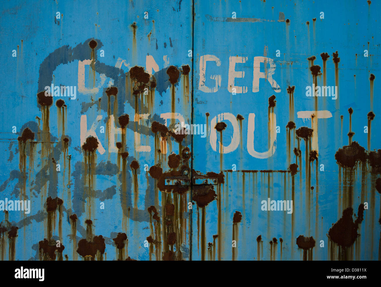 'Danger Keep Out' sign on blue door with rust patches, Oban, Argyll, Scotland - Stock Image