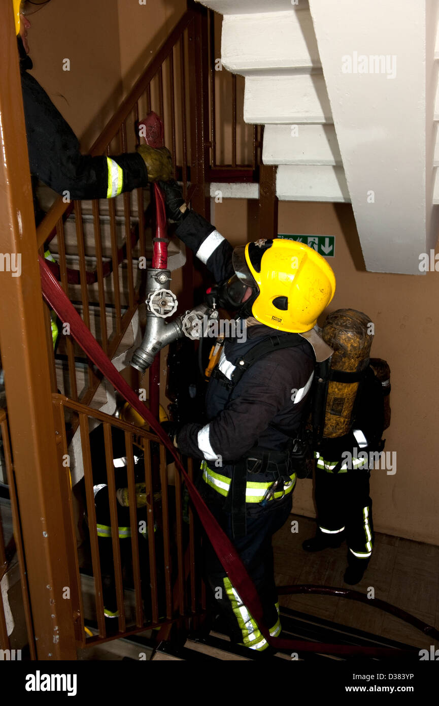Firemen laying hose in high rise flat fire - Stock Image