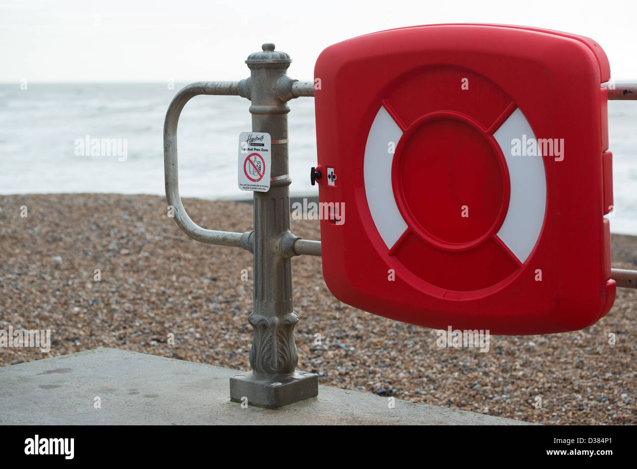 Life preserver / saver attached to railings on the beach in Hastings. Next to it is a sign banning alcohol consumption - Stock Image