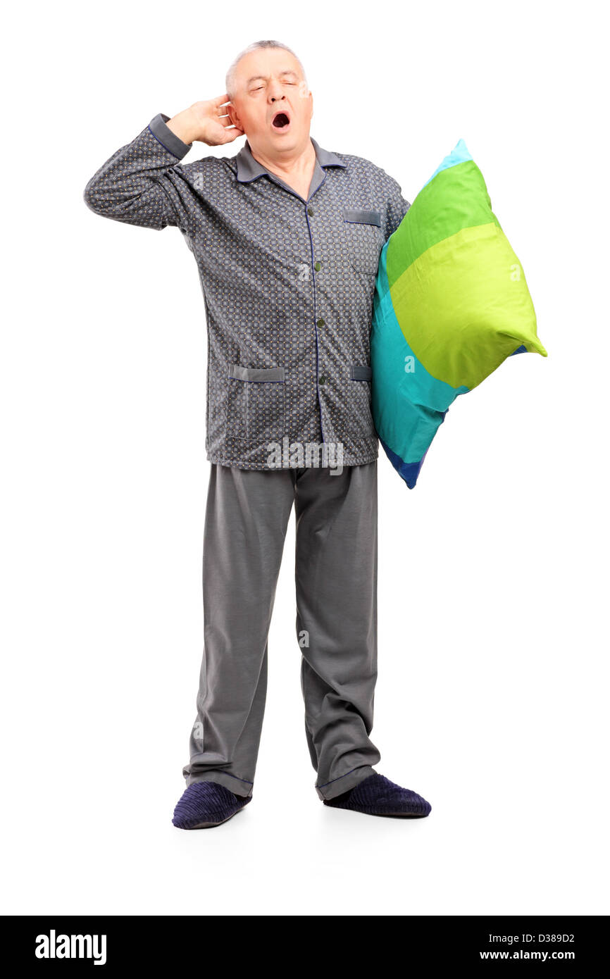 Full length portrait of a sleepy mature man in pajamas holding a pillow isolated on white background - Stock Image