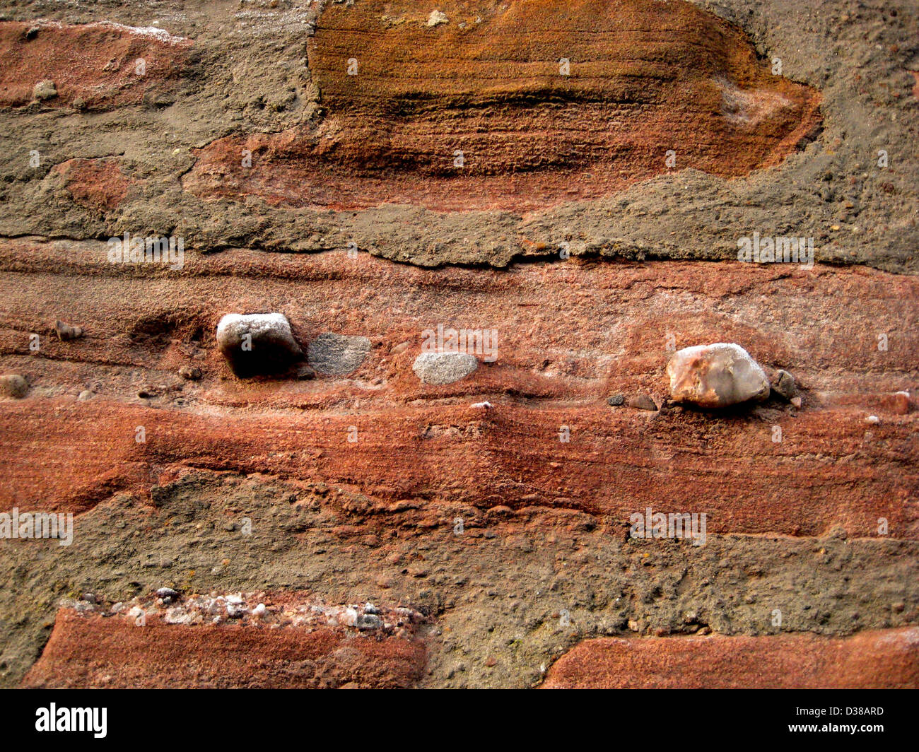A old red sandstone wall in the Scotland, showing pebbles weathering out from the strata, and lime mortar - Stock Image