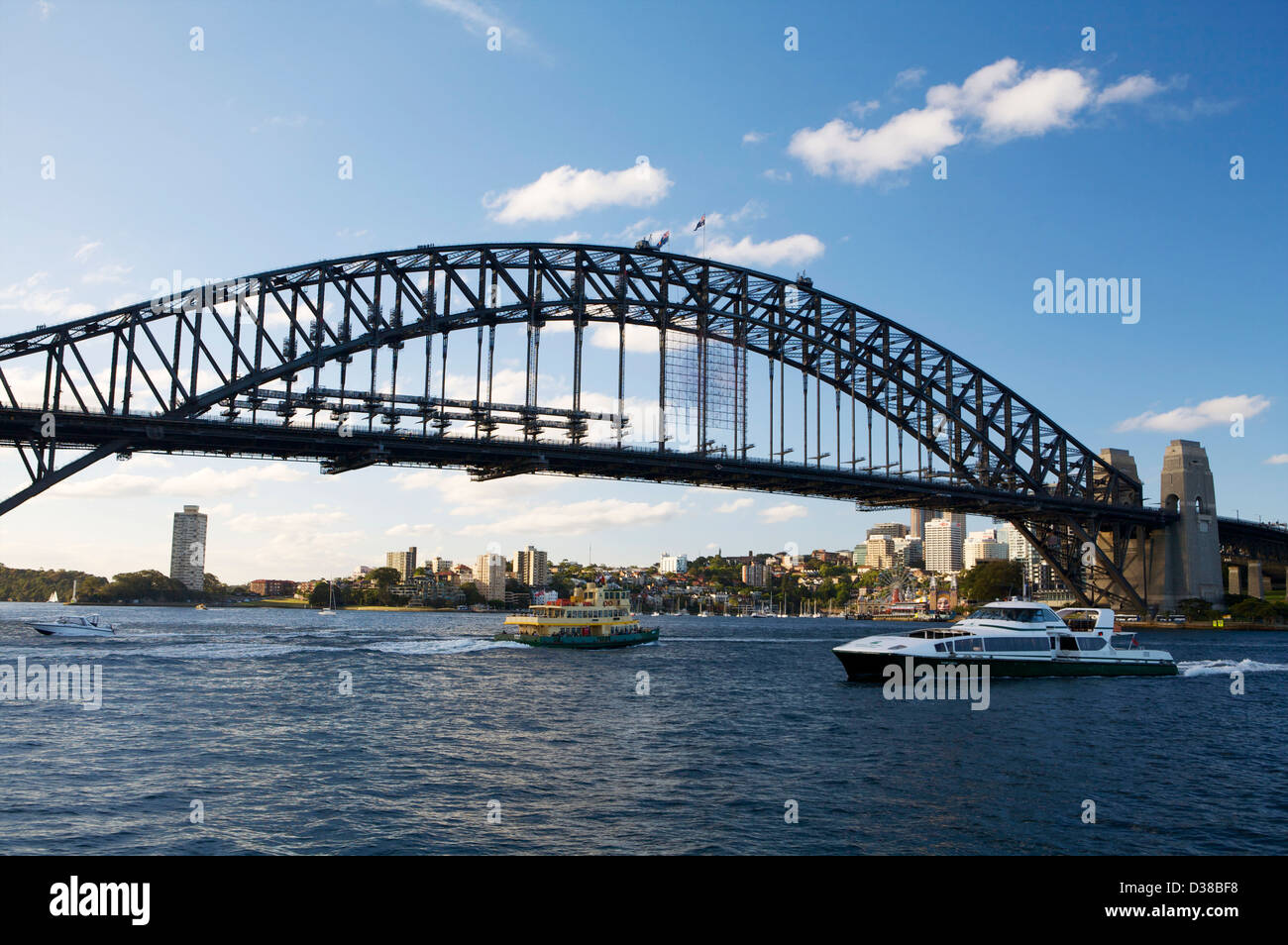 A view of the Sydney Harbor Bridge from the shoreline with public transportation ferries sailing below it. - Stock Image