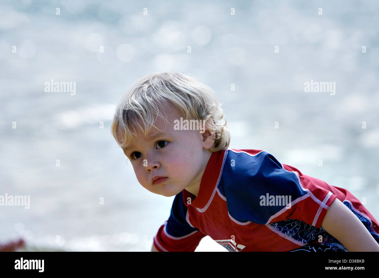 A small boy playing on the beach wearing a red and navy sun suit to protect him from the suns rays - Stock Image