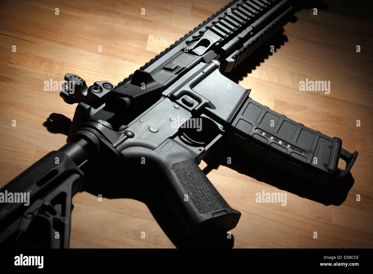 Modern custom AR-15 (M4A1) carbine on a wooden surface. Studio shot - Stock Image