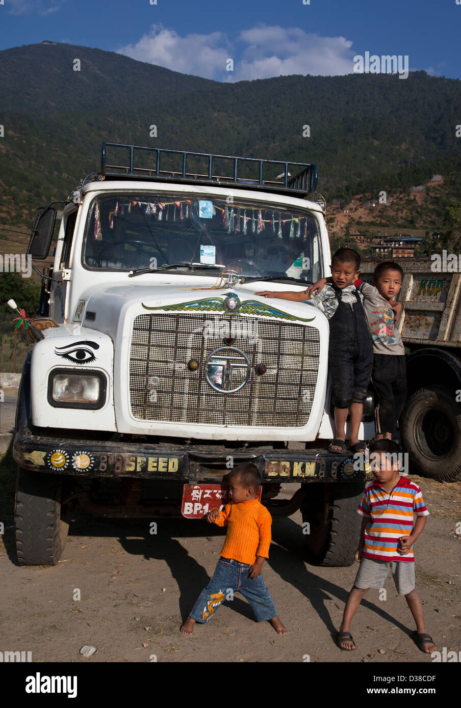 Kids playing with parked truck, Khuruthang, Punakha Dzongkhag, Bhutan - Stock Image