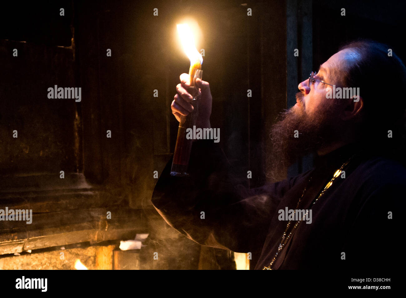 Jerusalem, Israel. 13th February 2013. A priest holds a candle and looks up at the Edicule of the Tomb in the Church Stock Photo