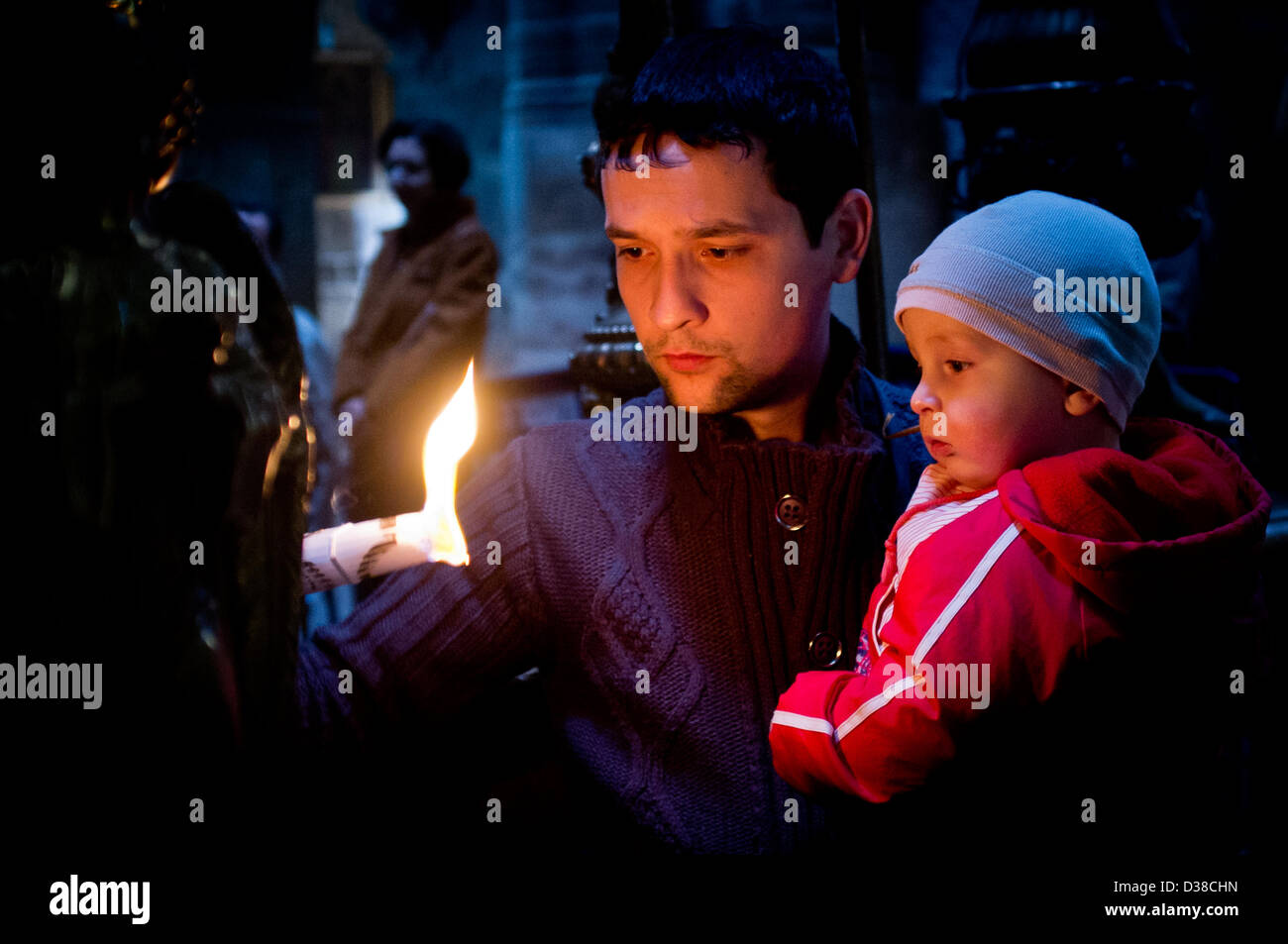 Jerusalem, Israel. 13th February 2013. A man holds a candle and his infant child by the Edicule of the Tomb in the Stock Photo