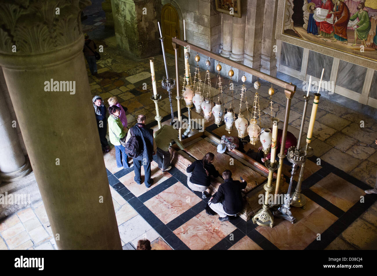 Jerusalem, Israel. 13th February 2013. Christian devotees kneel before the Stone of Unction, also known as the Stone Stock Photo