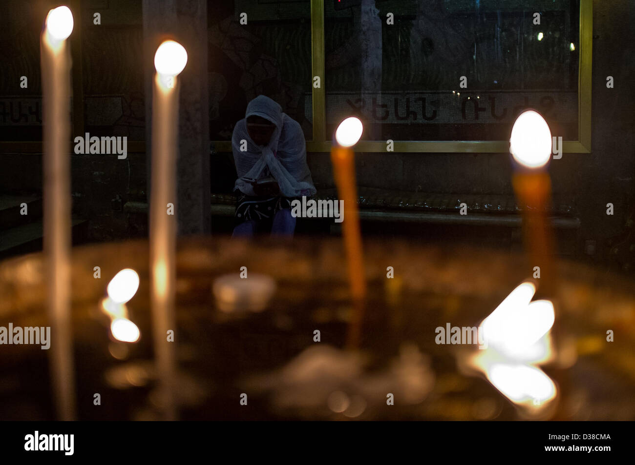 Jerusalem, Israel. 13th February 2013. A woman prays silently in the Church of the Holy Sepulchre on Ash Wednesday. Stock Photo