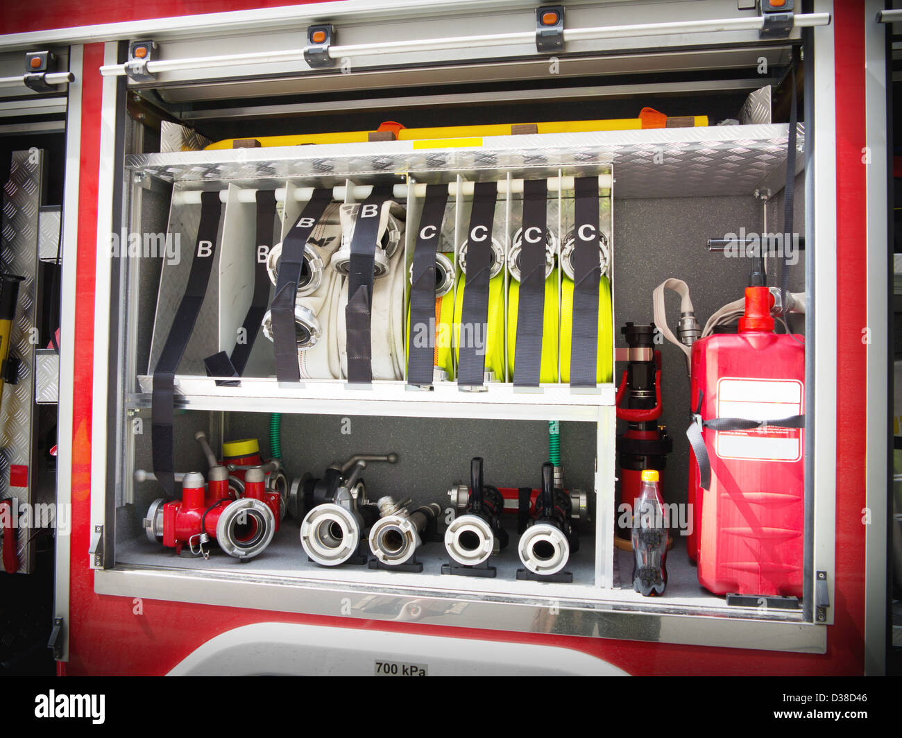 Fire valves and hoses on the side of a fire engine Stock Photo