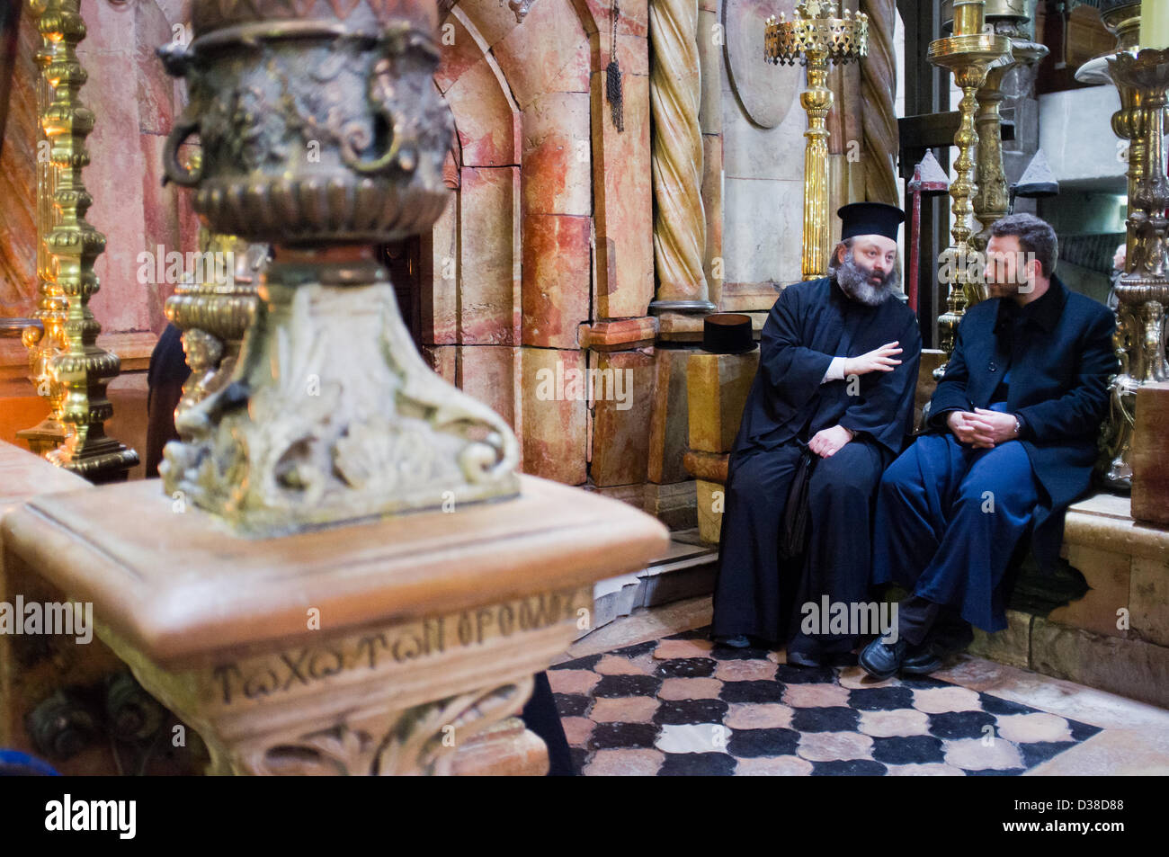 Jerusalem, Israel. 13th February 2013. Two priests converse at the entrance to what is believed to be the tomb of Stock Photo